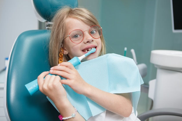 Funny little girl looking to the camera while brushing her teeth with electric toothbrush at dentists office