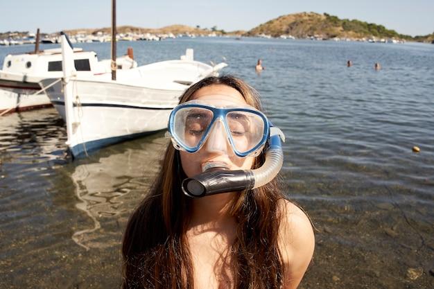 愚かな顔をしているダイビングマスクのビーチで面白い女の子。