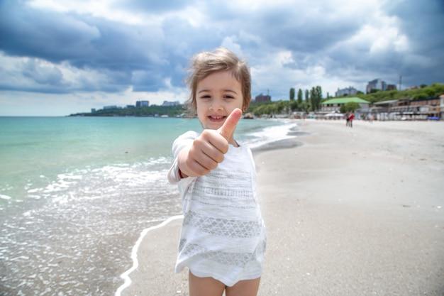 해변에서 재미있는 어린 소녀 미소 하 고 카메라에 보인다.