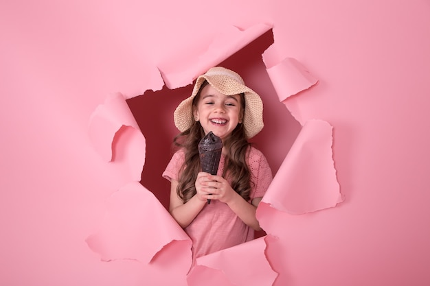 Funny little girl peeking out of the hole in a beach hat and ice cream in her hands, on a colored pink background, space for text, studio shooting