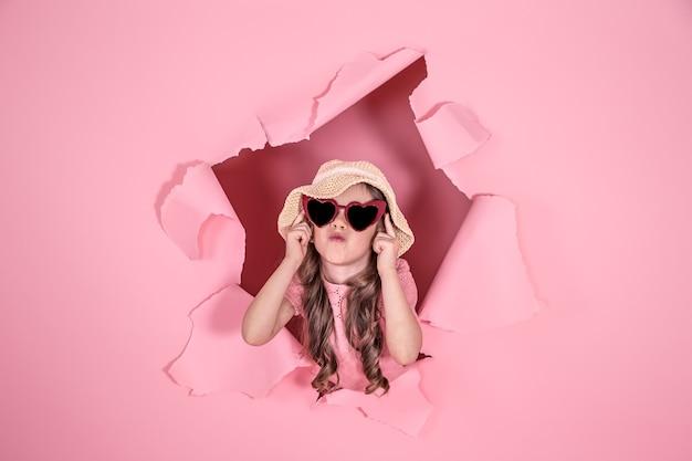 Забавная маленькая девочка выглядывает из дыры в пляжной шляпе и очках в форме сердца на цветном фоне, место для текста, студийная съемка