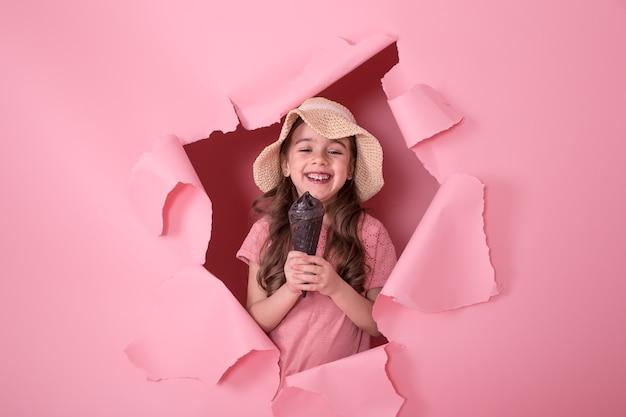Забавная маленькая девочка выглядывает из дыры в пляжной шляпе и мороженом в руках, на цветном розовом фоне, место для текста, студийная съемка