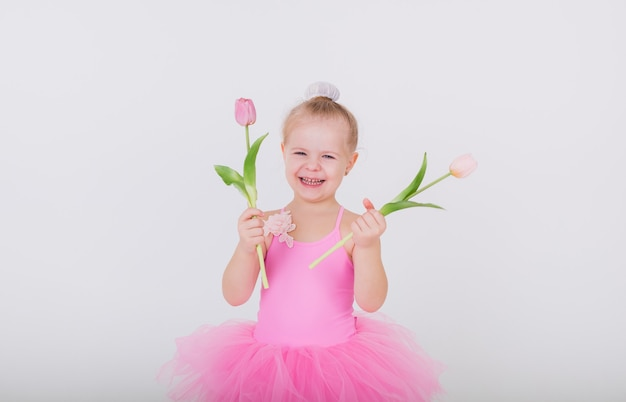 Funny little girl in a pink dress with tulips on a white wall