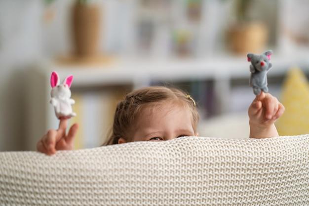 극장에서 노는 재미있는 작은 소녀. 손가락 인형은 어린이의 손에 놓입니다.