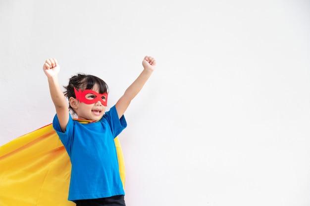 흰색 배경 위에 전원 슈퍼 영웅을 재생 하는 재미 있는 어린 소녀. 슈퍼 히어로 개념입니다.