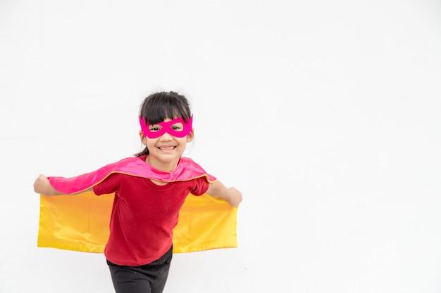 흰색 배경 위에 파워 슈퍼 히어로를 재생 하는 재미 있는 어린 소녀. 슈퍼 히어로 개념입니다.