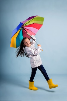 Funny little girl in rubber boots and with a multicolored umbrella is blown away by the wind on a blue background with a copy of the space