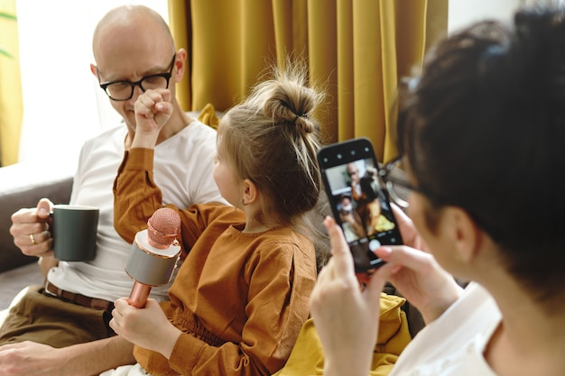 Смешная маленькая девочка показывает кулак отцу во время караоке-сессии