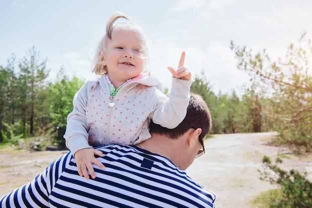 아버지의 어깨에 아이디어가 떠오른 것처럼 손가락을 보여주는 웃긴 소녀