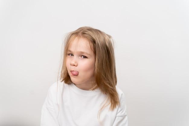 面白い小さな女の子は白い背景に舌を示しています。幸せな子供時代。子供のためのビタミンと薬。