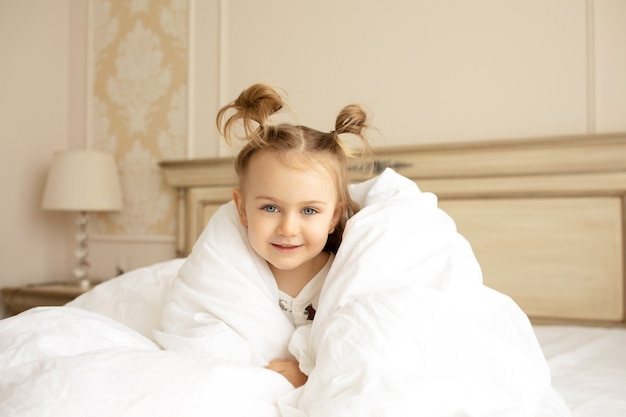 A funny little girl sits on a big bed under a white fluffy blanket in the room