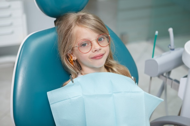 歯科用椅子に座っている面白い女の子