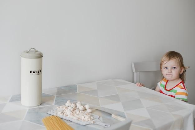 Смешная маленькая девочка сидит на кухне в ожидании ужина
