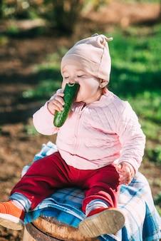 庭で新鮮なキュウリを食べる樽に座っている面白い少女