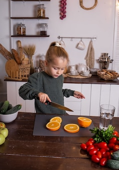 Funny little girl sitting at a wooden table and cutting an orange