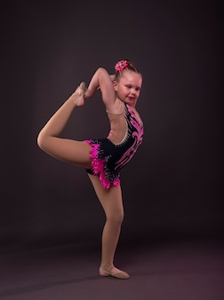 Funny little girl trying to do circle in gymnast black and pink costume in studio.