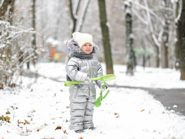 A funny little girl in a warm silver jumpsuit holds a toy shovel