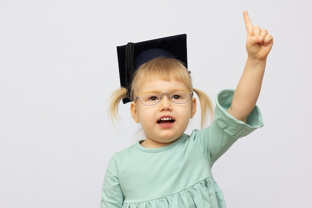 Funny little girl wearing eyeglasses imitates a teacher against white background. little student put finger up looking at camera. school concept. back to school