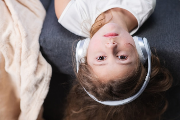 Funny little girl in wireless headphones dancing singing and moving to the rythm. little girl wearing headphones. kid in headphones. happy little girl listening to music with headphones
