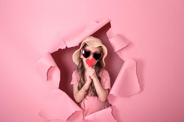Смешная маленькая девочка с сердцем на палочке на цветном фоне
