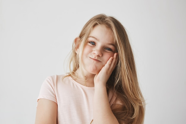Funny little girl with beautiful long blonde hair , squeezing cheek with hand, making funny face expressions, having fun..
