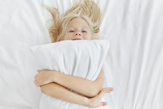 ブロンドの髪と青い目を持つ面白い女の子、ベッドで楽しんで、白い枕を抱きしめて、眠りにつく。自宅の枕で幸せな小さな子、寝室でリラックス。子供のライフスタイル