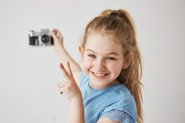 Funny little girl with blue eyes and light hair smiles, holding photocamera in her hand, showing v-sign, going to take selfie.
