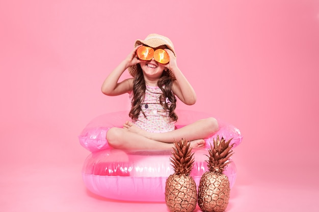 Funny little girl with citrus fruit on color