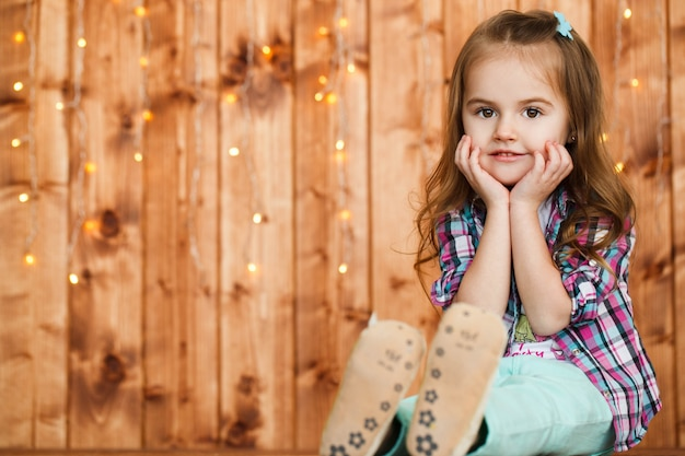 Funny little girl with dark blonde hair and nose painted in yellow