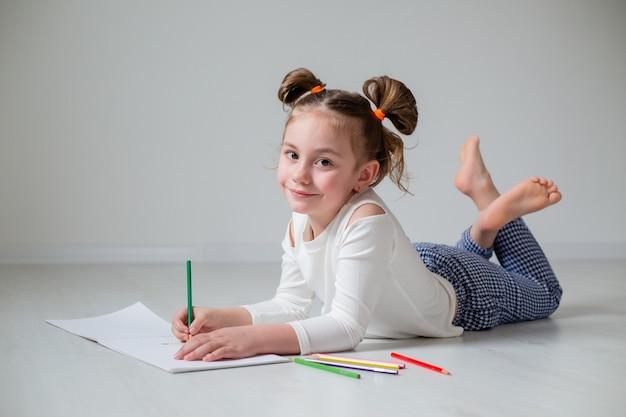 Смешная маленькая девочка в очках и необычной прическе лежит на деревянном полу домашнее образование
