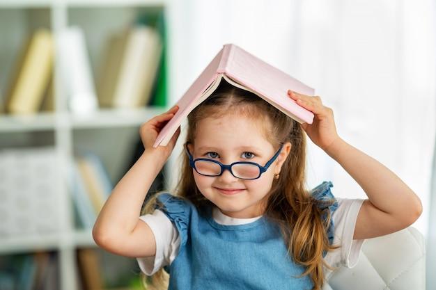 メガネと彼女の頭の上の本を持つ面白い少女