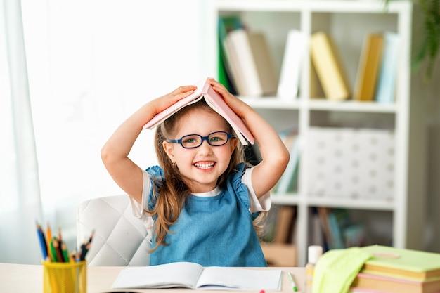 Смешная маленькая девочка с очками и книгой на голове