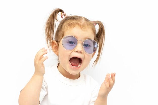 Смешная маленькая девочка в очках кричит, очень удивлена