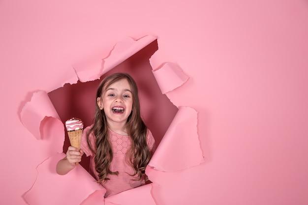 Смешная маленькая девочка с мороженым на цветном фоне