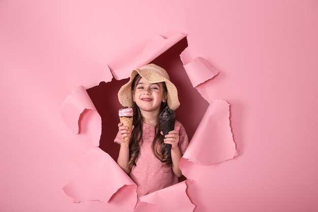 Забавная маленькая девочка с мороженым на цветном фоне