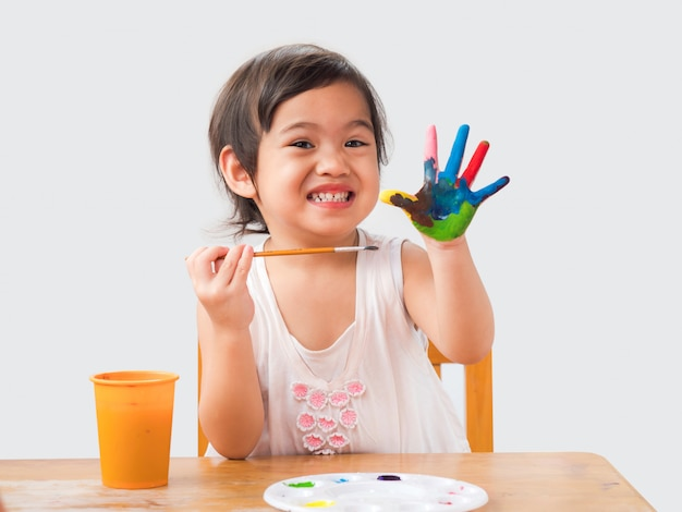 Funny little girl with painted hands on white backdrop.