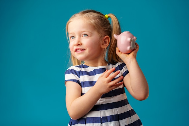 Funny little girl with piggy bank moneybox portrait
