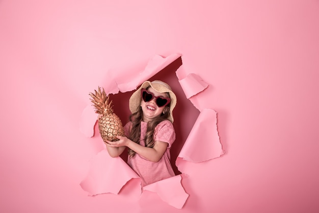 Funny little girl with pineapple on colored background