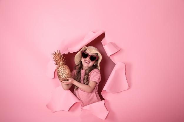 Смешная маленькая девочка с ананасом на цветном фоне