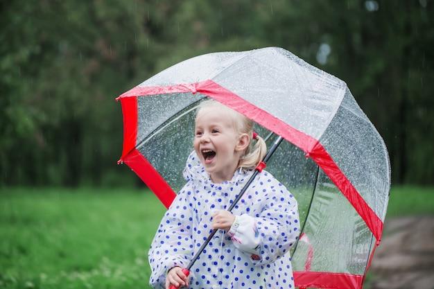 雨の中で傘を持つ面白い女の子