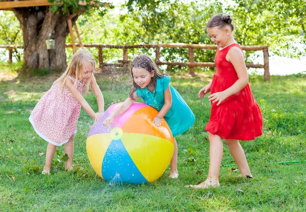 Funny little girls freands playing with a water ball in the sunny garden .
