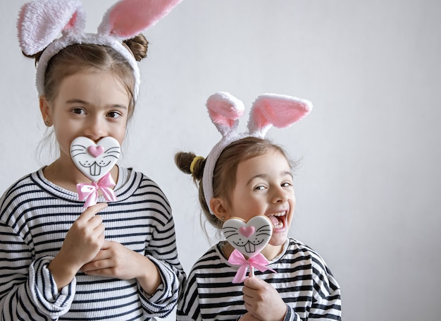 Funny little girls with easter ears on their heads and easter gingerbread on sticks