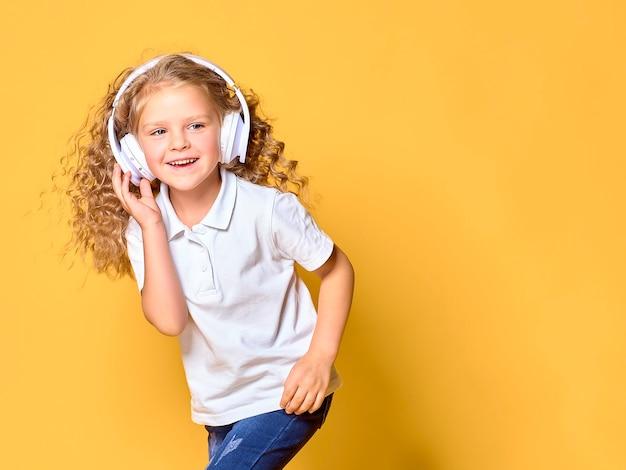 노란색 공간에 고립 된 흰색 티셔츠에 재미 있은 작은 아이 소녀