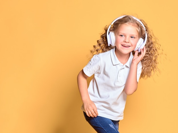 Funny little kid girl in white t-shirt isolated on yellow space. childhood lifestyle concept. mock up copy space. listen music in headphones, dancing with fluttering hair