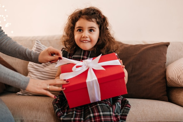Funny little kid holding birthday present. curly preteen girl with gift sitting on sofa.