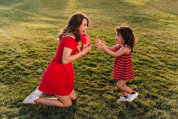 お母さんと夏の日を楽しんで赤いドレスを着た面白い小さな子供。草の上で娘と遊ぶゴージャスなブルネットの女性の屋外写真。
