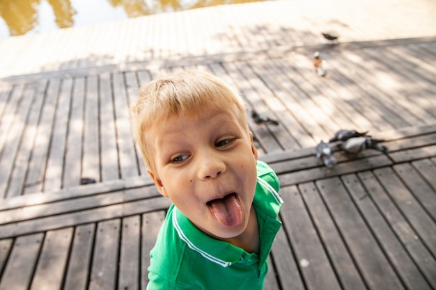 公園で舌を示す面白い小さな子供