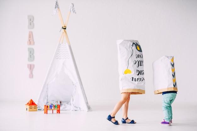 아이들의 wigwam에 머리에 종이 봉투가있는 밝은 방에서 재미있는 작은 아이들