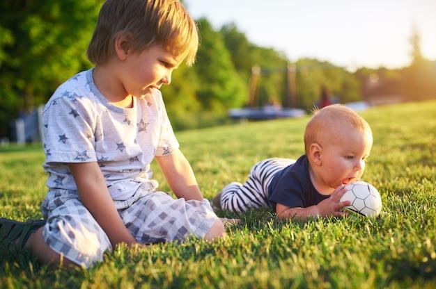 여름 날에 자연에 푸른 잔디에 공을 가지고 노는 재미 작은 아이. 두 형제는 야외. 유치원 소년과 아기. 정원에서 노는 아이들.