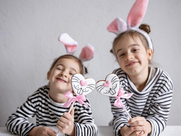 Забавные сестренки с пасхальными пряниками в виде зайчиков-мордашек и с заячьими ушками
